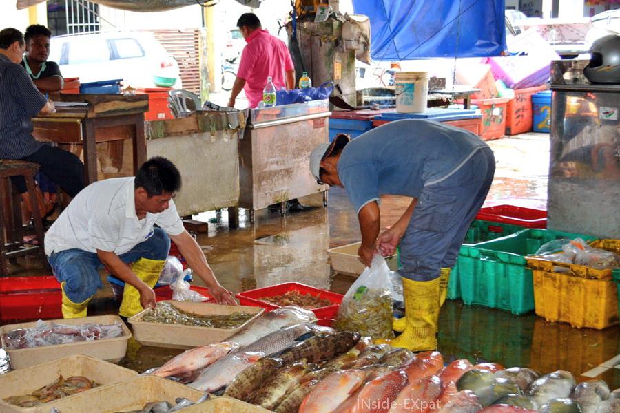 Vendeurs malais sur un marché de poissons à Pontian