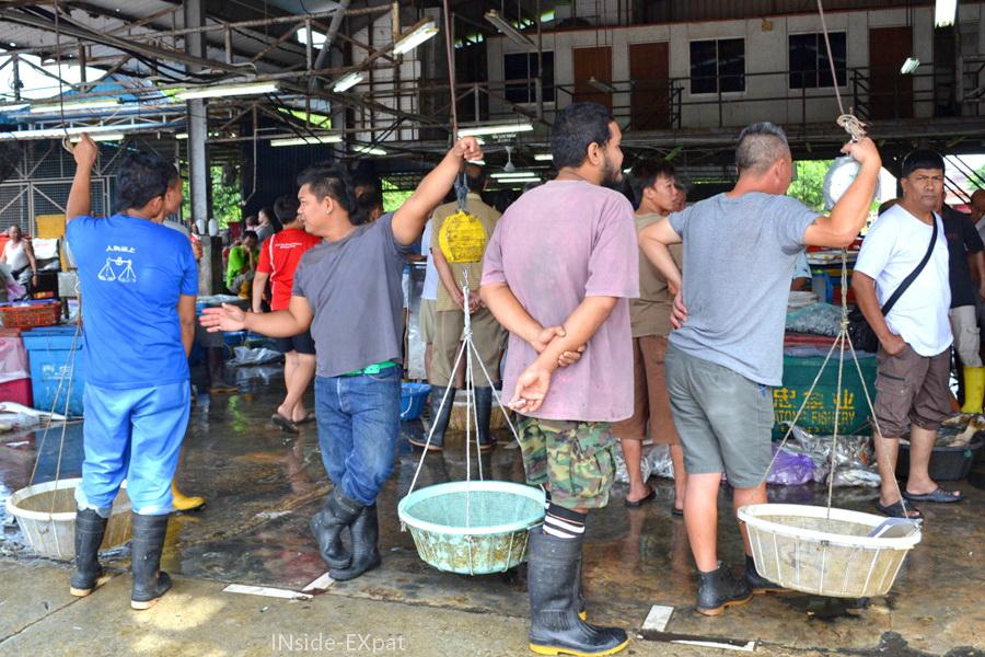 Hommes malais sur le grand marché de poissons de Pontian