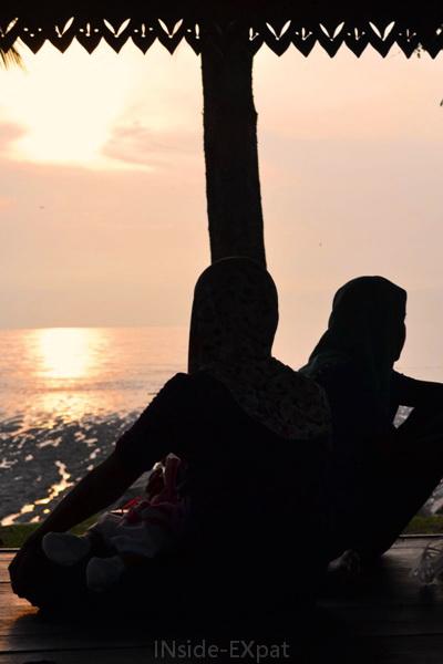 Femmes malaises regardant le coucher de soleil