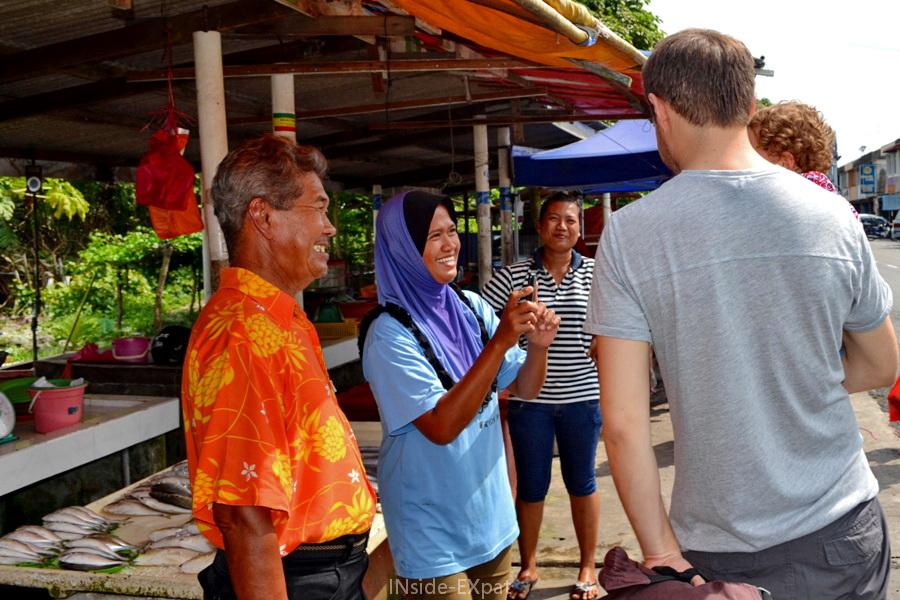 Discussion entre touristes et locaux sur un marché de Pontian en Malaisie