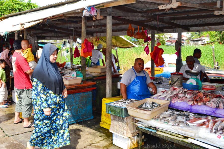 Vendeurs et acheteurs d'un petit marché local à Pontian en Malaisie