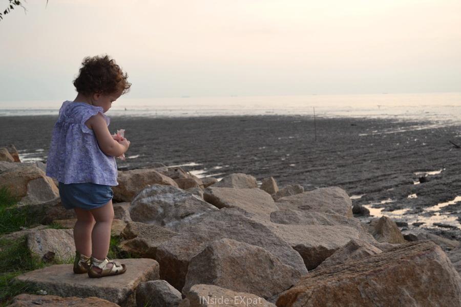 Petite fille sur une digue face à la mer