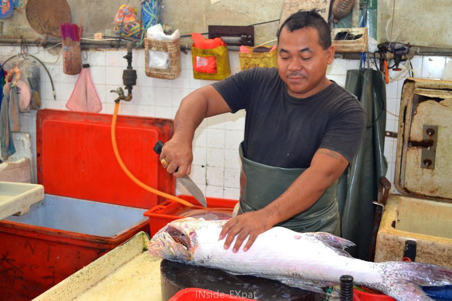 Un vendeur malais découpe un poisson sur un marché de Pontian.