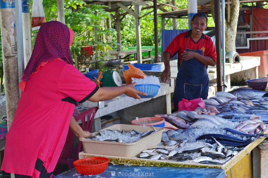 Des vendeurs remettent de la glace sur leur étal de poissons