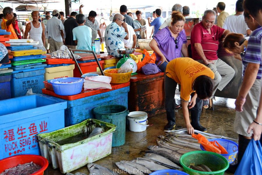 Acheteurs et vendeurs sous les halles du grand marché de poissons de Pontian