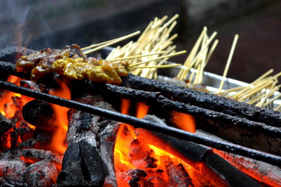 Brochettes de satay en train de cuire sur le feu