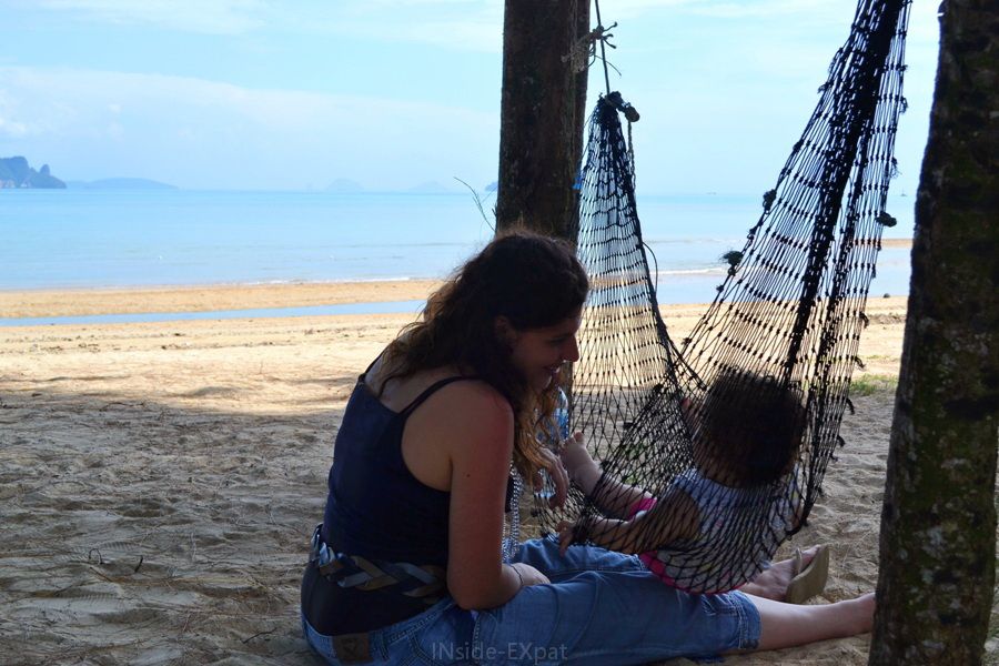 Bébé dans un hamac et sa maman face à la plage