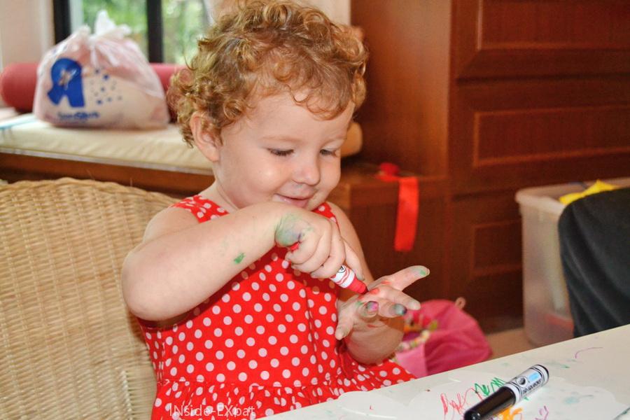Petite fille se coloriant les mains au feutre