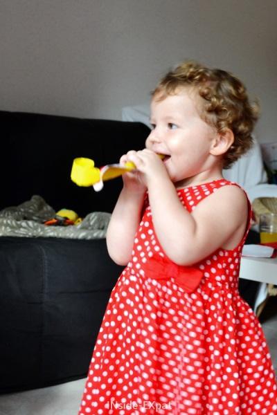Petite fille en robe rouge à pois blanc qui joue