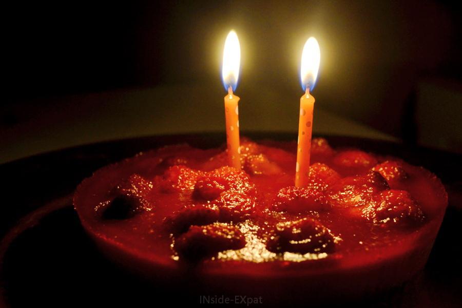 Gateau d'anniversaire dans le noir éclairé par deux bougies
