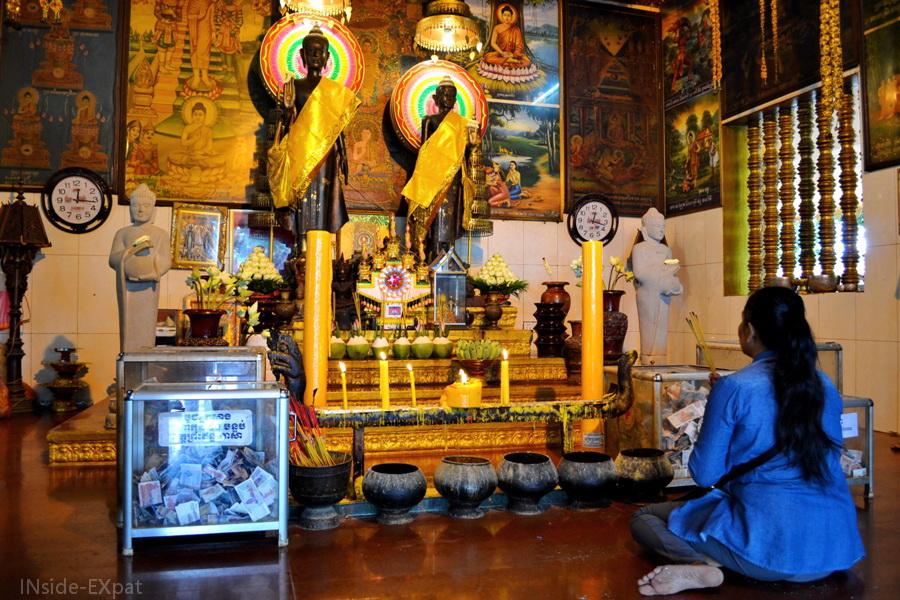 femme qui prie dans un temple bouddhiste