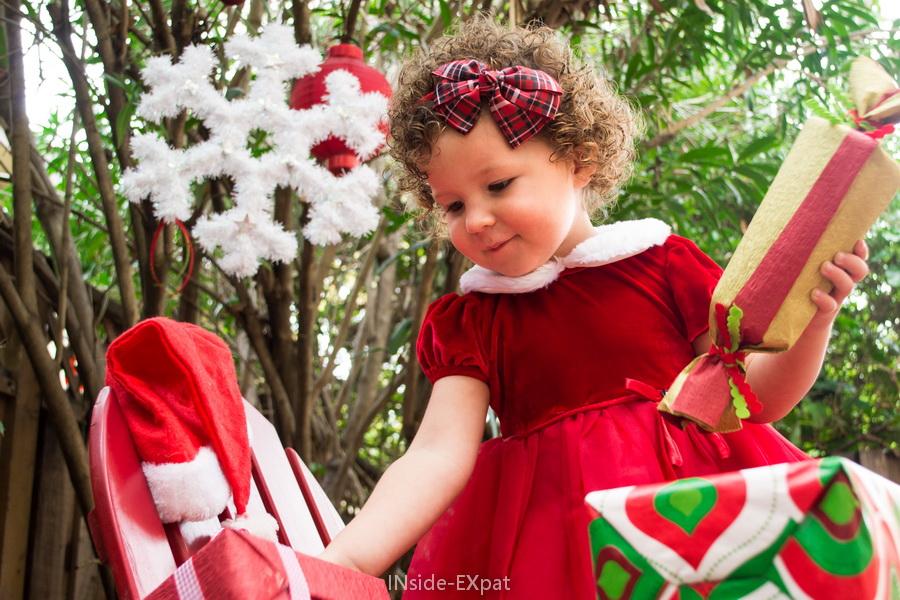 Petite fille au milieu de ses cadeaux de Noël