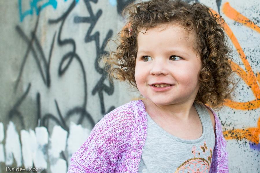 Petite fille devant des graffitis
