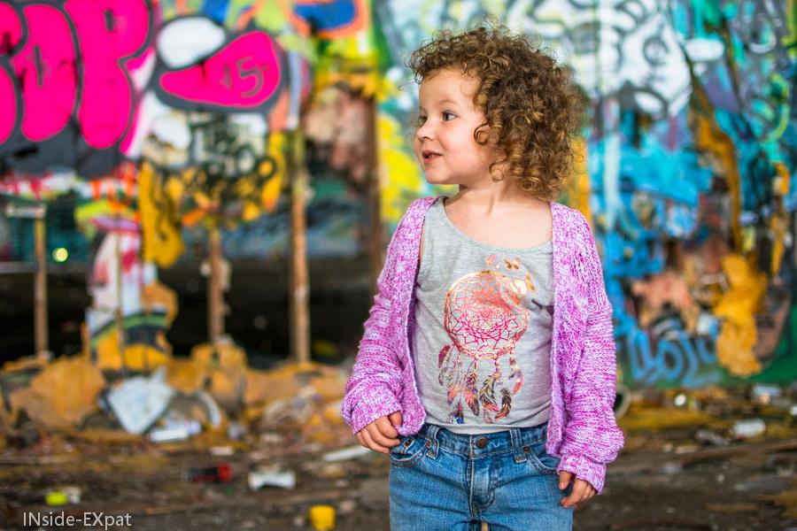 Mimi devant un mur tagué